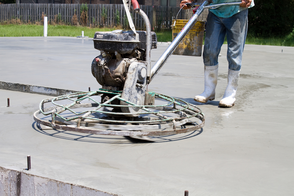 Picture of our employee using a motorized power trowel to smooth and finish concrete at a new home site is Dayton, OH